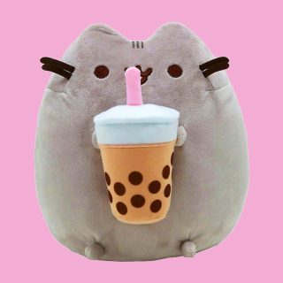 Pusheen the cat can't resist a yummy boba tea! This gorgeous plush kitty is holding a cup of boba tea with a pink straw in between her front paws.