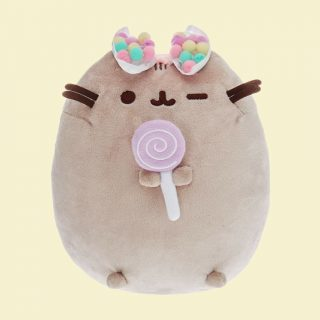 Pusheen is the sweetest cat and this plush soft toy is even sweeter holding a purple lollipop and wearing a colourful rainbow pom pom bow on her head.