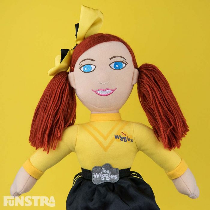A yellow bow, long red hair and wearing her signature yellow shirt and black skirt with the official logo belt buckle.