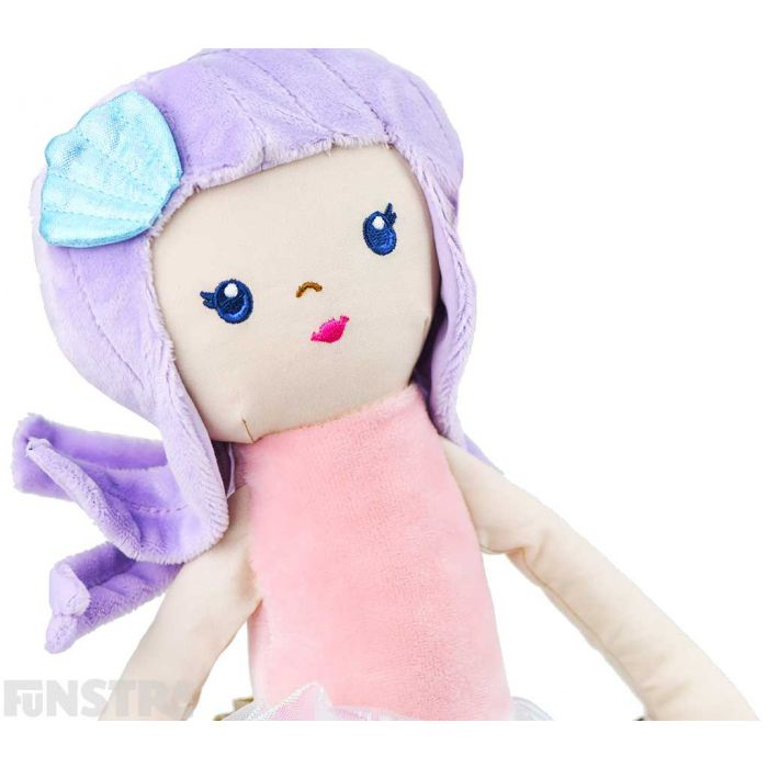 A sparkly seashell hair accessory in her purple hair and beautifully embroidered facial features, the plush mermaid is stunning.
