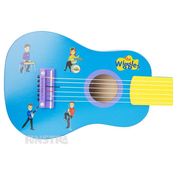 Lachy, Emma, Anthony and Sam are singing and playing musical instruments on the body of the guitar.